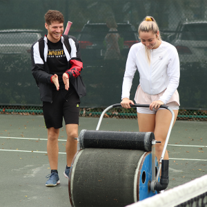 Gaccione and teammate help dry the courts at the 2020 Tennis on Campus Delray Beach Challenge