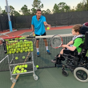 Wheelchair player practicing with a certified tennis professional